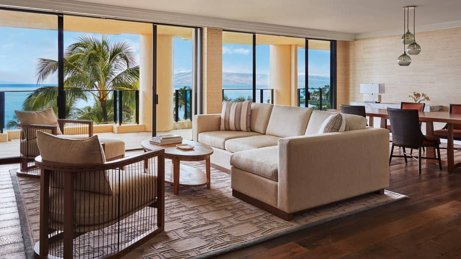 Elite Two-Bedroom Suite living room with white sofa and wood chairs, four-person dining table, balcony