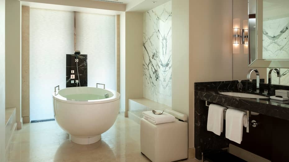 Grand Premier Room free-standing round white tub and shower in black-and-white marble bathroom
