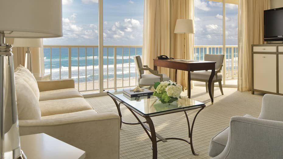 Oceanfront Suite with white sofas and chairs, office desk with lamps, floor-to-ceiling balcony windows