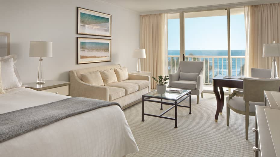 Premier Ocean-View Room with ivory sofa, ocean-inspired art and juliet balcony with beach view