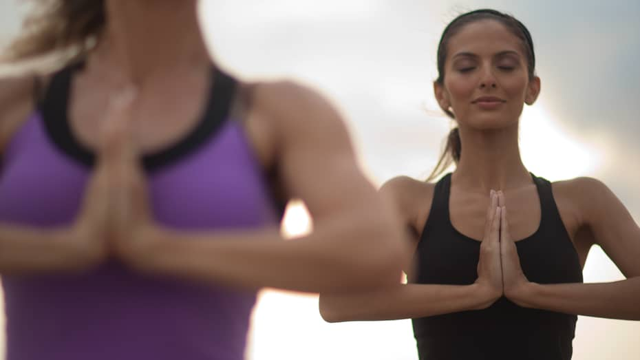 Two women with eyes closed stand with hands together in yoga pose