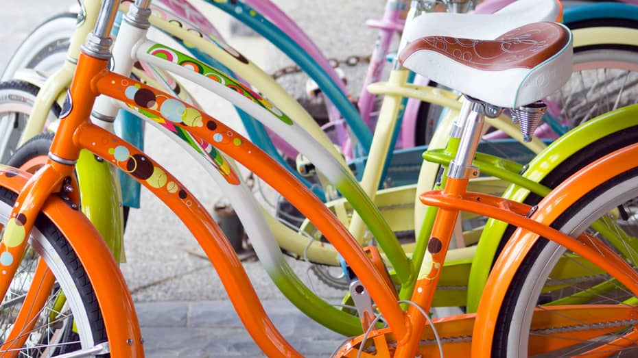 Row of colourful bicycle frames in bright orange, green, yellow, blue and pink