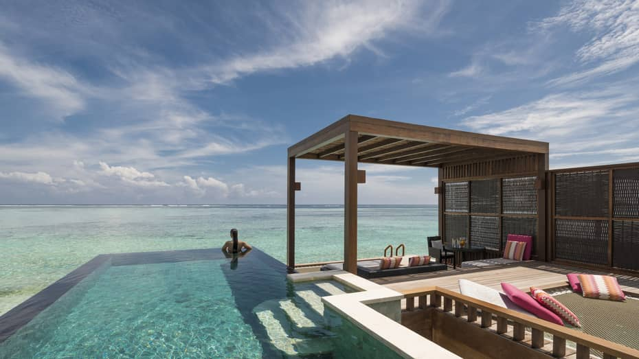 Woman looks out at ocean from private pool on sunny patio of sunset water villa