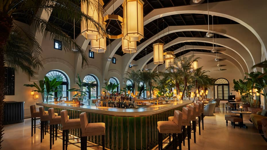 Evening view of Le Sirenuse indoor Champagne bar, stools and palms lining white bar