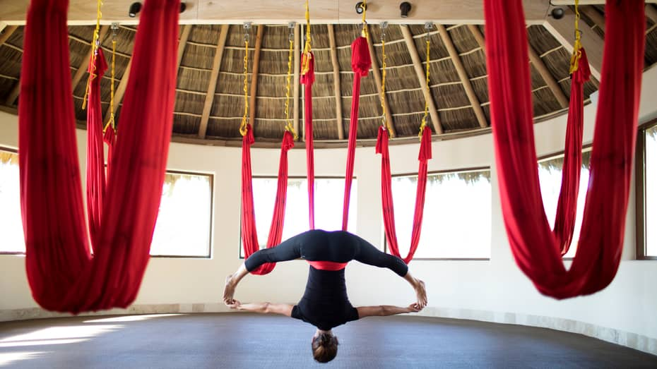 Woman hangs upside-down from red fabric in anti-gravity yoga pose, red fabric hammocks hang from thatched roof