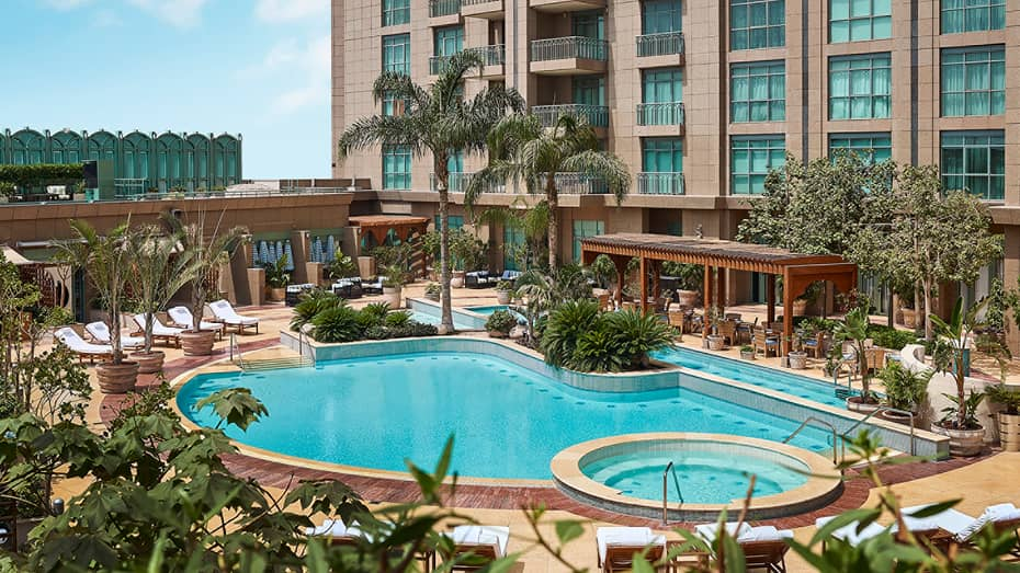 Wide view of outdoor swimming pool lined with tropical plants, cabanas and hotel tower and balconies overhead