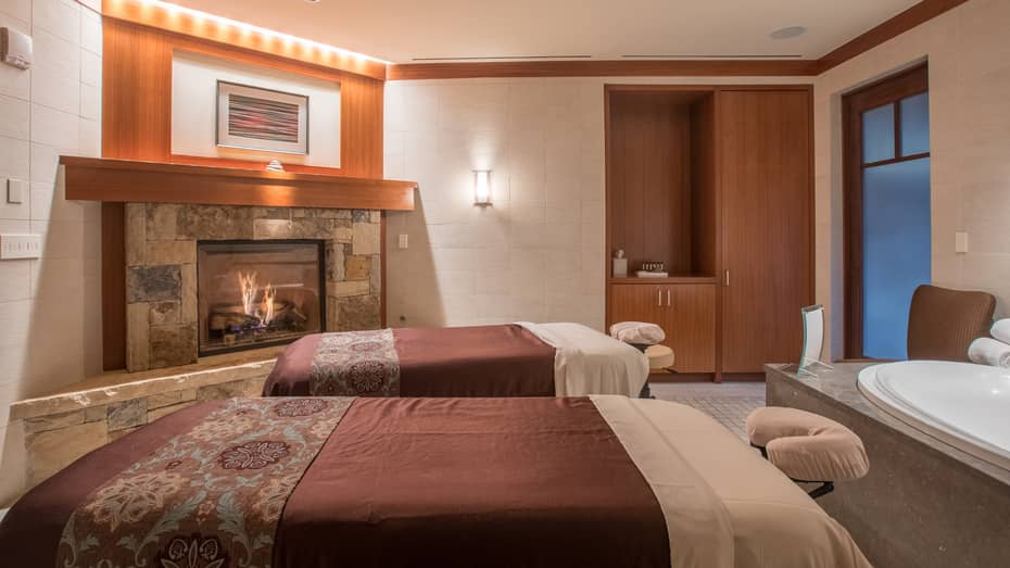 Two couples massage tables with red blankets in front of spa tub and gas-burning fireplace