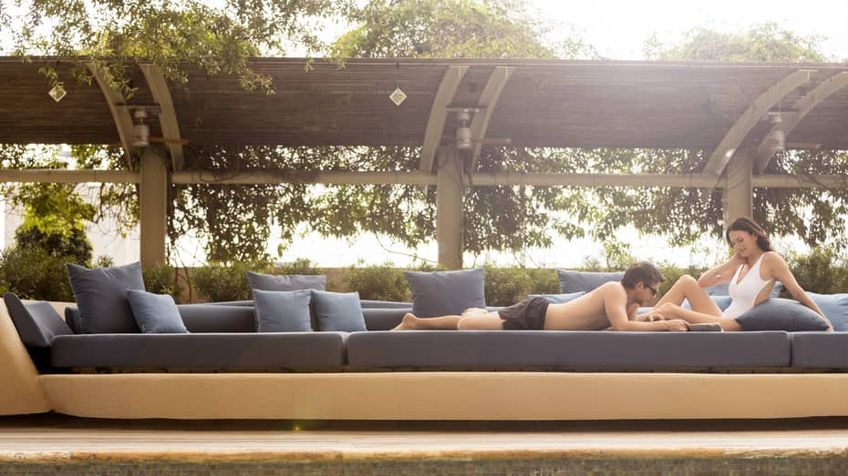 Man in swim trunks and woman in white swimsuit sunbathe on large blue patio banquette