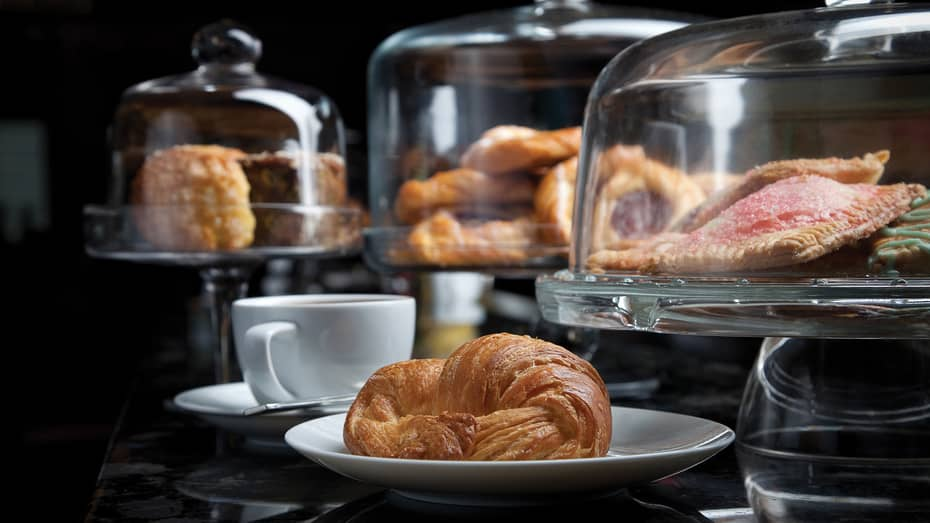 Glass display cases with pastries, croissant on white plate beside white coffee mug