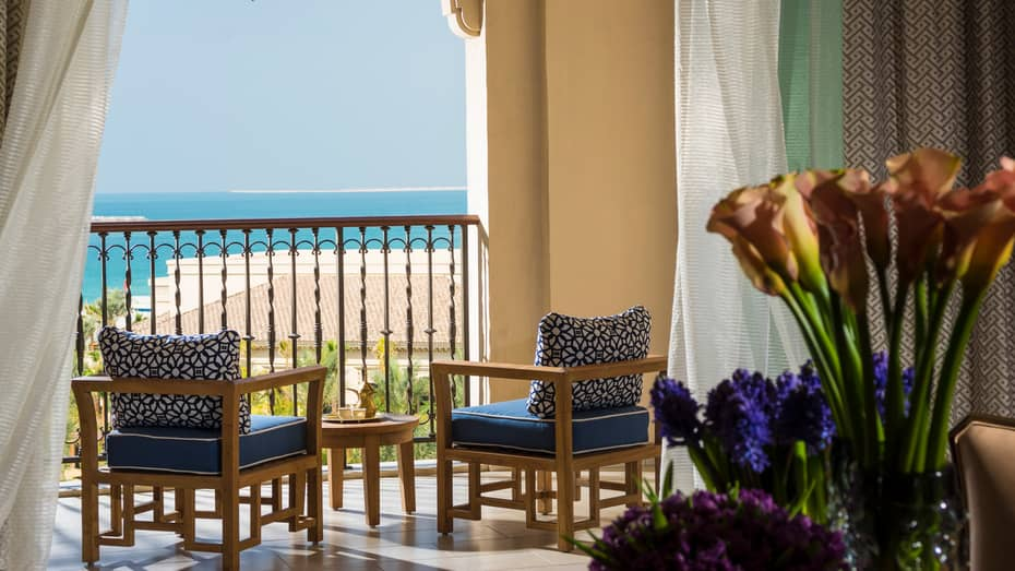 Imperial Suite with blue and purple flowers, sunny balcony with wood furniture, blue cushions