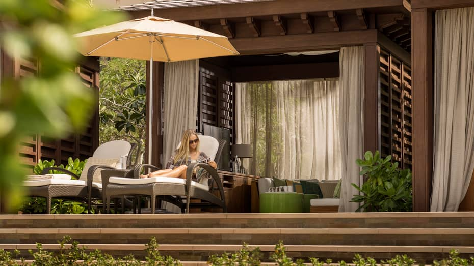 Woman reads magazine on lounge chair under white patio umbrella and poolside cabana