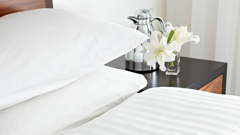 Close-up view of presidential suite bed with white linens, fresh white lilies and steel carafe on bedside table