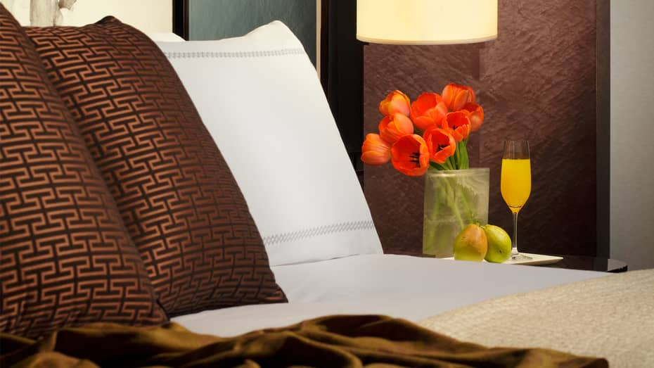 Deluxe Room close-up of white and brown pillows on bed with red tulips and mimosa glass on bedside table