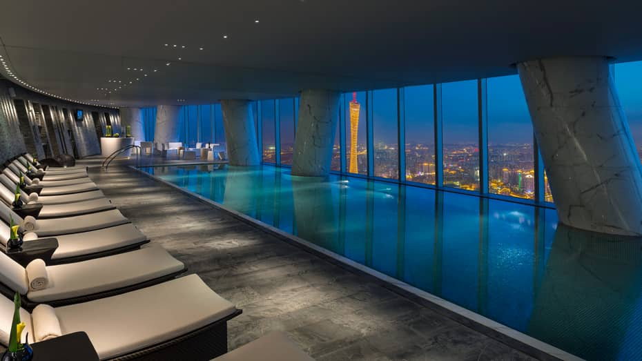 White chairs and indoor pool on 69th floor at night, beside windows overlooking city lights and Pearl River
