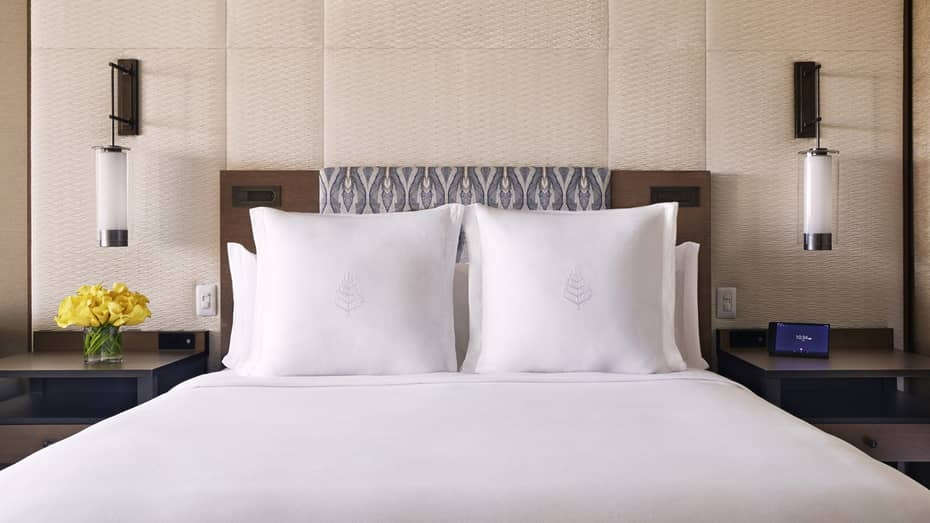Partial Ocean-View room bed with white pillows with Four Seasons logo, wood headboard, wall panel