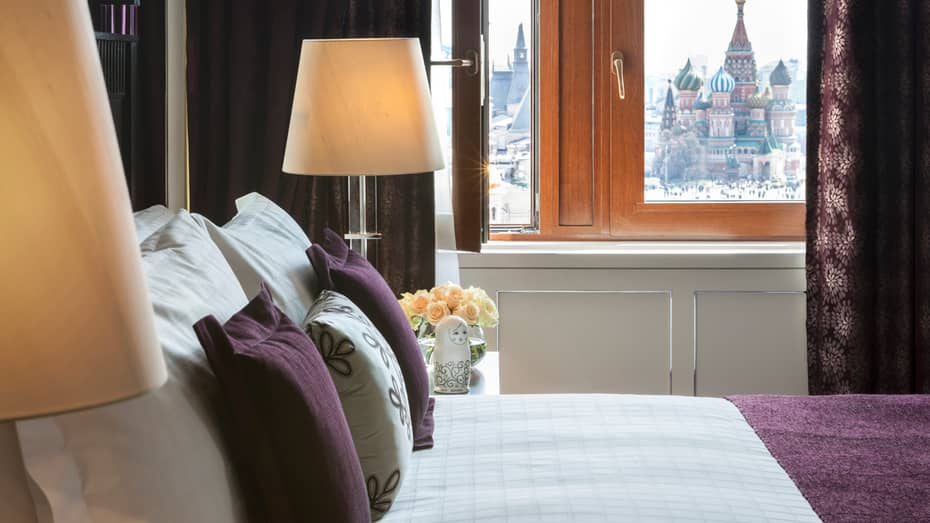 White bed with purple pillows, white Russian doll on nightstand, St. Basil's Cathedral seen through window