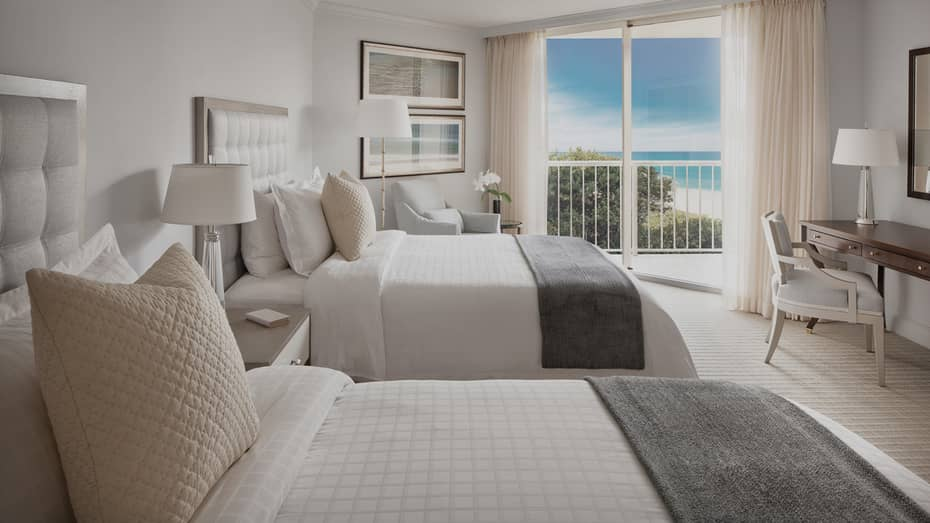 Ocean-View Room with double beds, grey padded headboards and gold pillows, balcony door with beach view