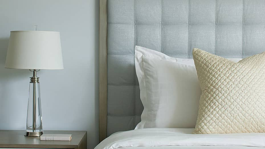 Close-up of Accessible Ocean-View Room with white bed, ivory accent pillow, grey padded headboard, lamp