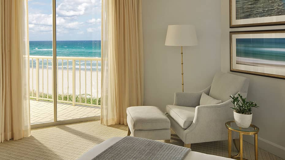 two bedroom suite. White armchair next to glass balcony door with view of ocean and beach Deluxe Two Bedroom Suite Palm Beach  Four Seasons Resort