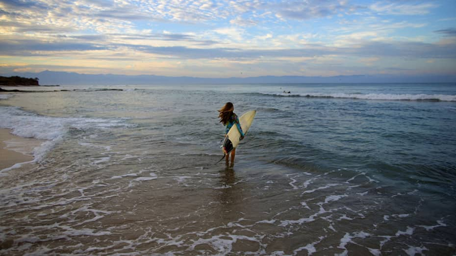 Woman with white surfboard walks into ocean tide at sunset