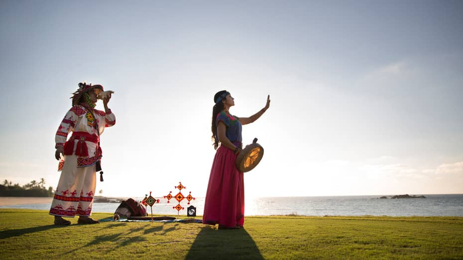 Man and woman perform native Huichol traditions on grass near beach and ocean