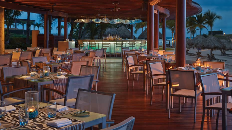 Bahia seafood restaurant open-air dining room and bar at dusk, palm trees and beach in view