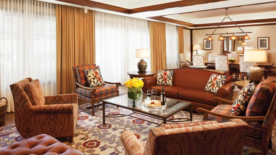 Gore Range Wing living area with red sofa, paisley and plaid armchairs, large windows behind curtains