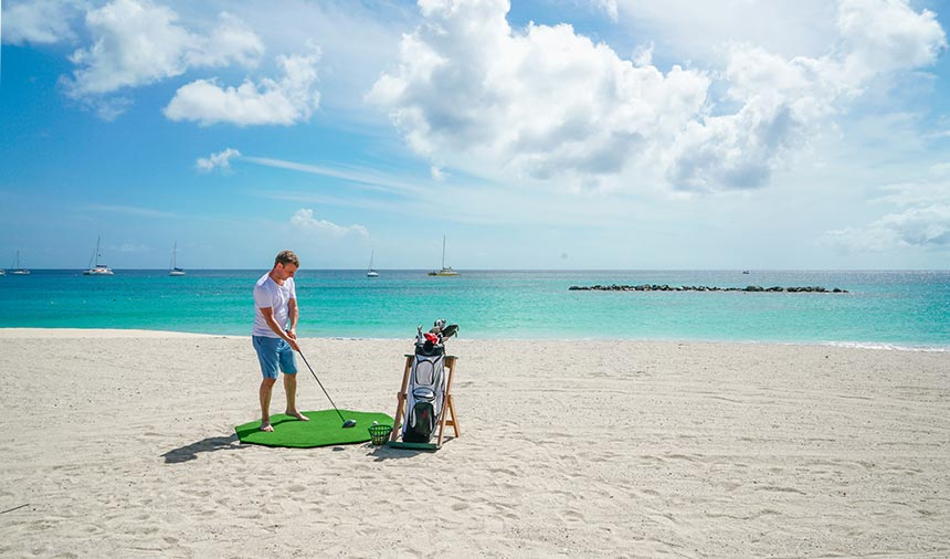 A person is hitting biodegradable golf balls into the Nevis ocean